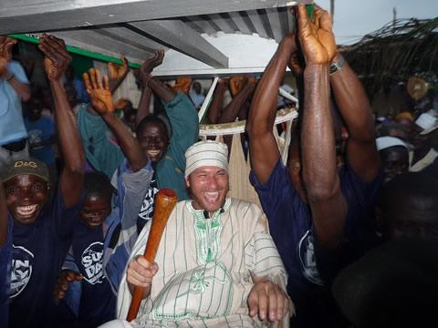 Traditie in Sierra Leone: Uit respect wordt een nieuwe Chief een rondje gedragen in een hangmat